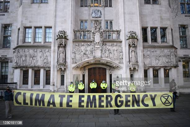 Campaingers against a proposed third runway at Heathrow hold placards outside the Supreme Court in London on December 16, 2020 as police officers...