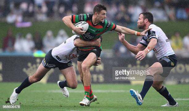 Campbell Graham of the Rabbitohs is tackled by Gavin Cooper and Lachlan Coote of the Cowboys during the round 16 NRL match between the South Sydney...