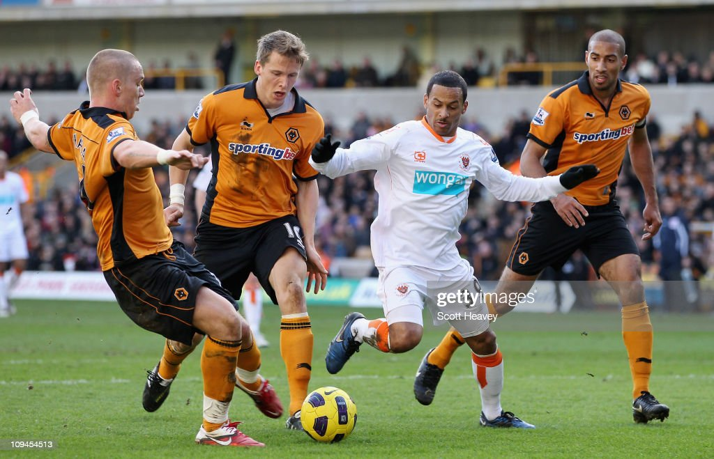 DJ Campbell of Blackpool (C) is tackled by Jamie O'Hara of Wolves (L) during the Barclays Premier League match between Wolverhampton Wanderers and Blackpool at Molineux on February 26, 2011 in Wolverhampton, England.