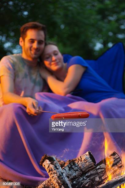 Camper Couple Roasting Hotdogs on Campground Vertical
