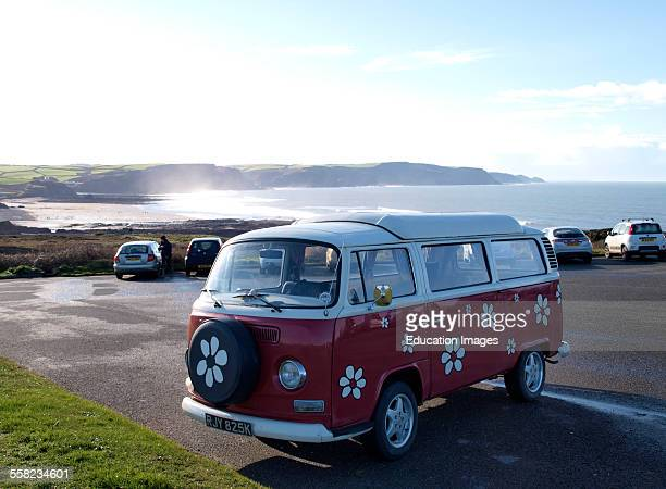 VW camper in car park overlooking the sea Widemouth Bay Cornwall