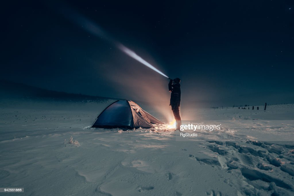 Camper lighting camp site with a battery lamp : Stock Photo