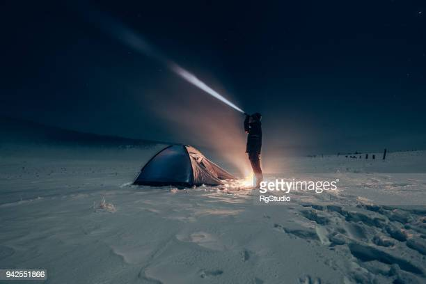 Camper lighting camp site with a battery lamp