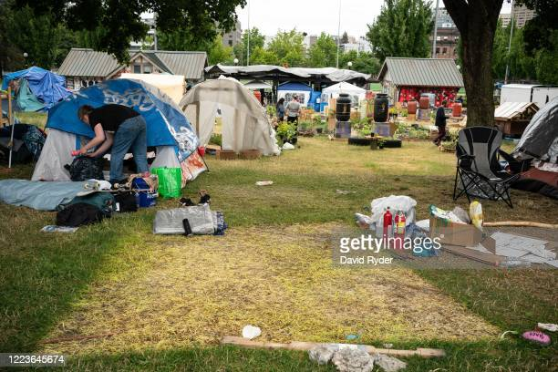 Camper packs up belongings while preparing to leave, near the site of a recently removed tent, in Cal Anderson Park in the Capitol Hill Organized...