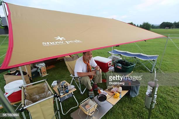 Camper sits under a tarp at the Snow Peak Inc. Camp field n Sanjo, Niigata Prefecture, Japan, on Tuesday, Aug. 2, 2016. Snow Peak, which makes...
