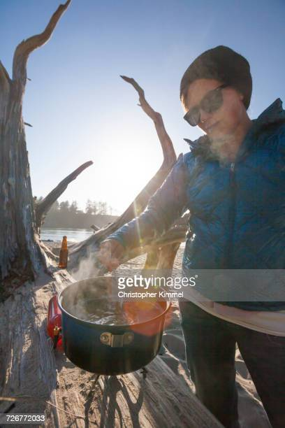 a camper stirring a pot while making dinner on the beach - sunset bay state park stock pictures, royalty-free photos & images