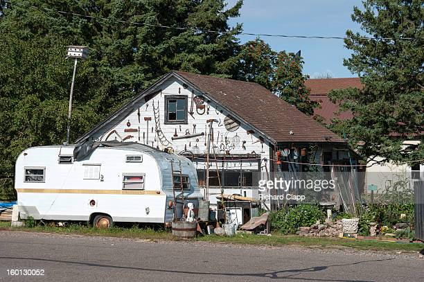 CONTENT] A camper trailer parked in front of a garage covered with antique farm and forestry implements Lifestyle in a north western Wisconsin small...
