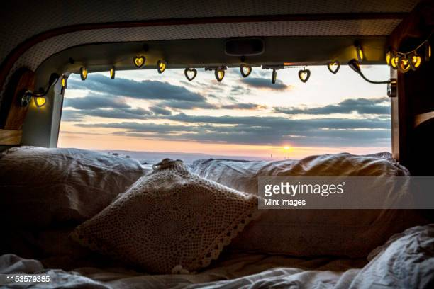 camper van with cushion and fairy lights, view through rear window at sunset. - vehicle interior stock pictures, royalty-free photos & images