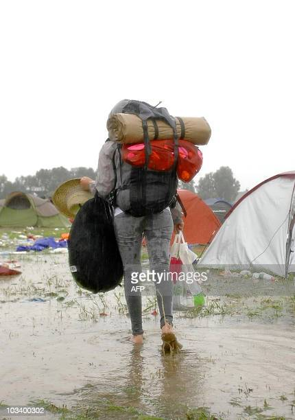 A camper walks on August 16 2010 in a flooded camping site at the festival Feest in het Park after heavy rainfall in Oudenaarde Some 2000 people were...