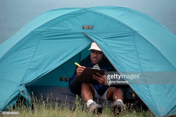camper writing in tent - ポーキュパイン山脈ウィルダネス州立公園 ストックフォトと画像