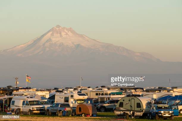 Campers form Solar Town an agricultural field turned campground for total solar eclipse enthusiasts in front of Mt Jefferson in Madras Oregon on...