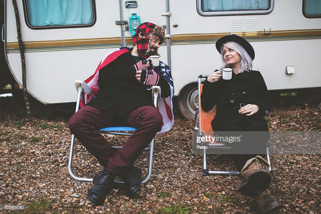 Campers holding steel mugs warming up near fire : Stock Photo