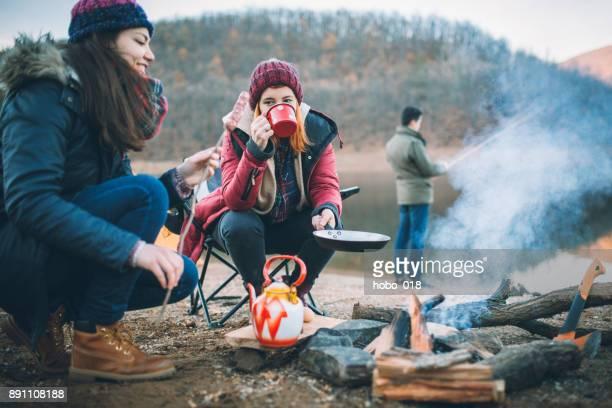campistas junto a la fogata preparando la comida - camping fotografías e imágenes de stock