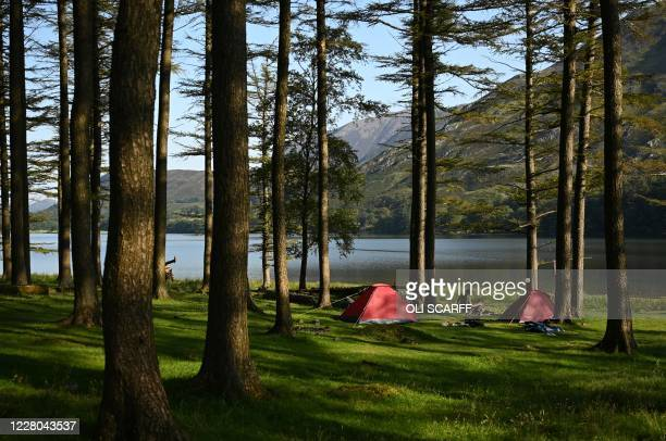 Campers relax early in the morning beside Buttermere Lake in the Lake District in north west England on August 14 as many people take advantage of...