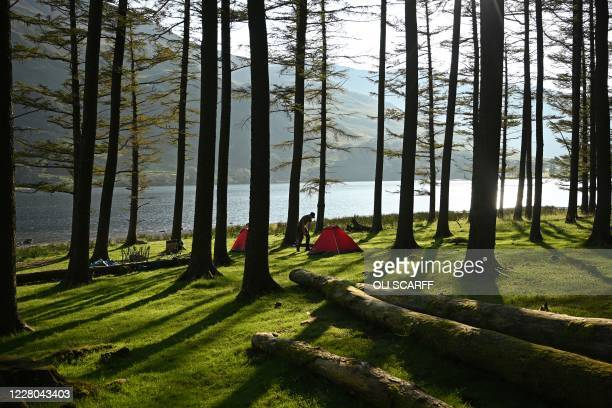 Campers wake as the sun rises over Buttermere Lake in the Lake District in north west England on August 14 as many people take advantage of the...
