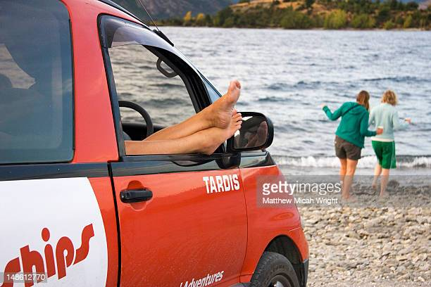 Campervan with feet sticking out window by Lake Wanaka.
