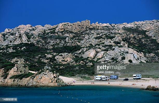 Campervans along the beach on the rocky lunar landscape of Isola Maddalena.