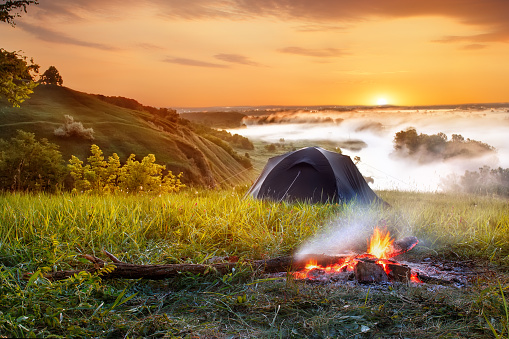 campfire and tent at sunrise 693244226