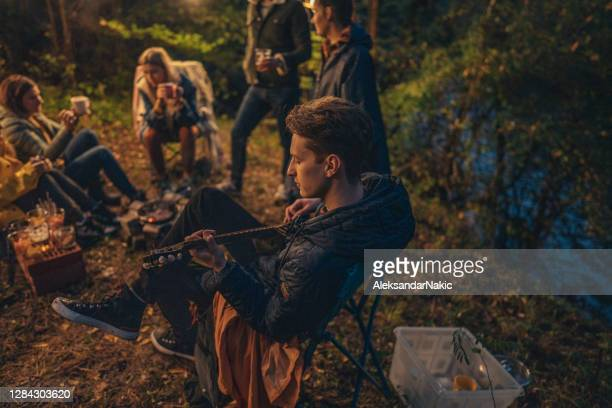campfire guitarist - adventure stock pictures, royalty-free photos & images