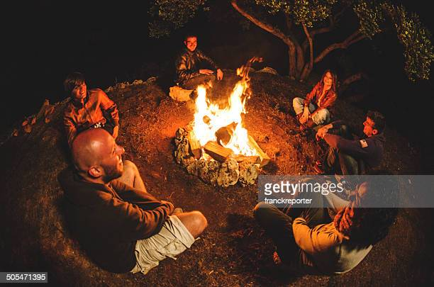 campfire of friends in circle on the fire - campfire stock pictures, royalty-free photos & images