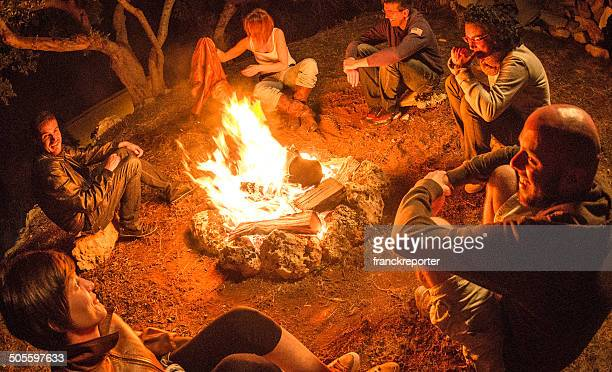 campfire of friends in circle on the fire - camp fire stock photos and pictures