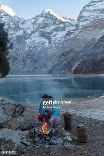 Campfire on Lake Oeschinen, behind it Blueemlisalphorn, Bernese Oberland, Switzerland
