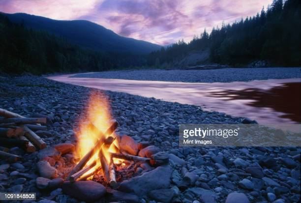 Campfire on the bank of the South Fork of the Flathead River  In the Bob Marshall Wilderness Area of Montana, USA