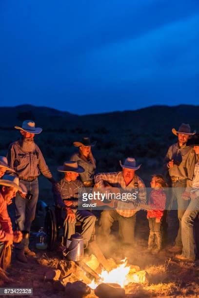 singalong de la fogata con vaqueros y vaqueras por la noche - stringed instrument fotografías e imágenes de stock