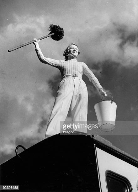 Camping. A camper is standing with swab and bucket on her caravan. Photograph. 1937.