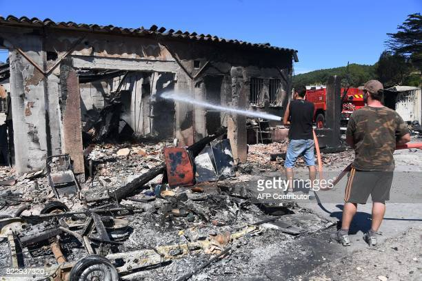 Camping and caravaning guard company owners try to extinguish a fire burning in BormeslesMimosas southeastern France on July 26 2017 At least 10000...