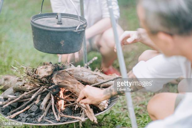 シチュースープディナーのために大釜で調理するために薪を使用してアジアの中国人をキャンプ - 薪 ストックフォトと画像