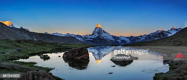 Camping at Matterhorn during sunrise with Stellisee in foreground