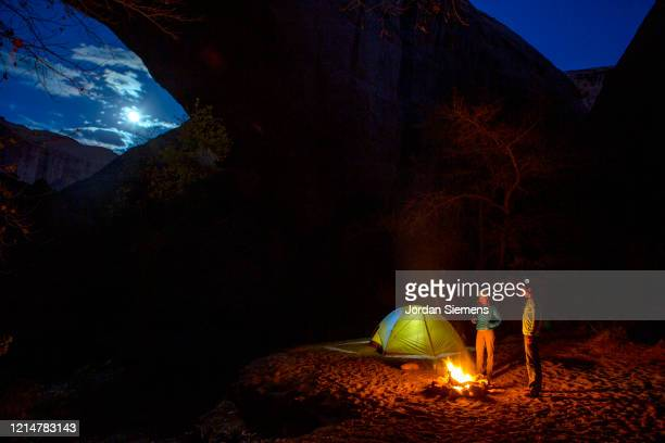 camping at night in a light up tent under a giant desert arch. - st. george utah stock pictures, royalty-free photos & images