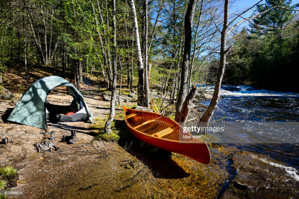 Camping at the riverbank with a canoe : Stock Photo