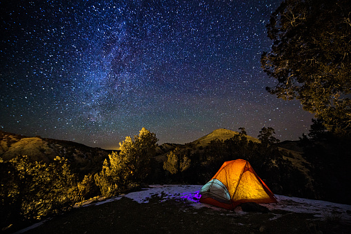 Camping in a Tent Under the Stars and Milky Way Galaxy 904960682