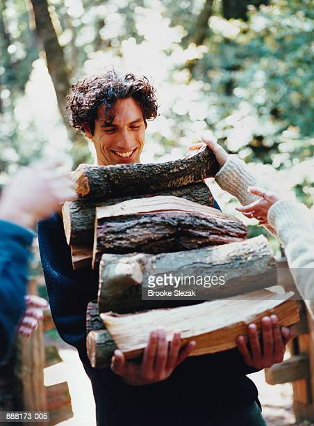 Camping, man carrying logs for fire