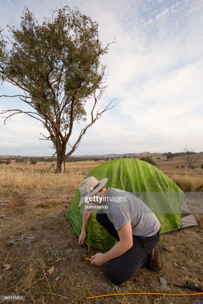 C&ing man hammers his tent peg into hard ground  Stock Photo & Camping Man Hammers His Tent Peg Into Hard Ground Stock Photo ...