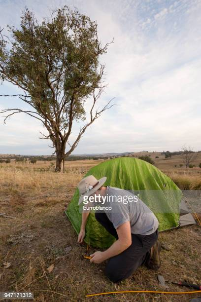 Camping man hammers his tent peg into hard ground