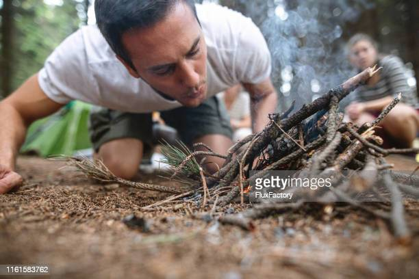 camping man making a campfire - survival stock pictures, royalty-free photos & images