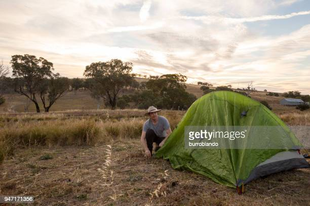 Camping man sets up his tent in the yellow afternoon light