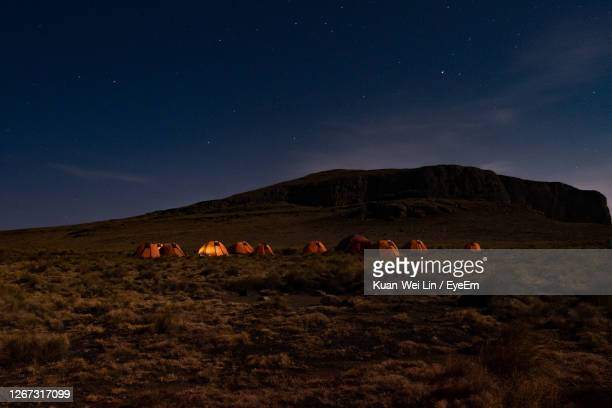 camping on top of mountain on a starry night  with glowing tent - south africa stock pictures, royalty-free photos & images