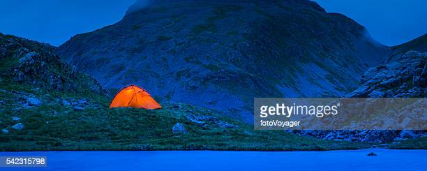 Camping tent illuminated against blue dusk mountains panorama Lake District