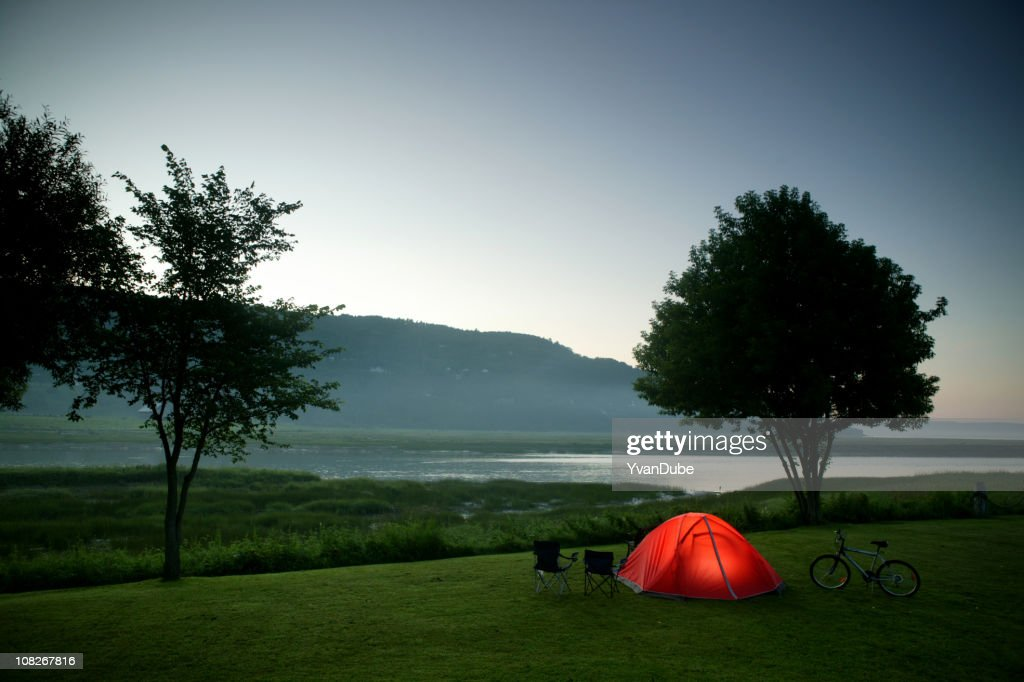 camping tent nearby river and mountain at night : Stock Photo