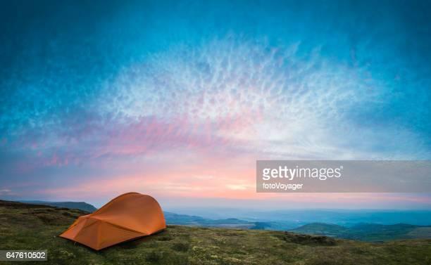 Camping Zelt am grünen Berg mit Blick auf ruhigen Tal bei Sonnenuntergang