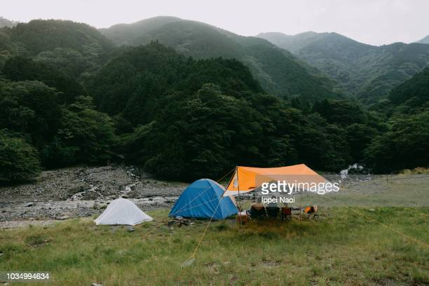 Camping tents and tarp by river surrounded by mountains, Japan