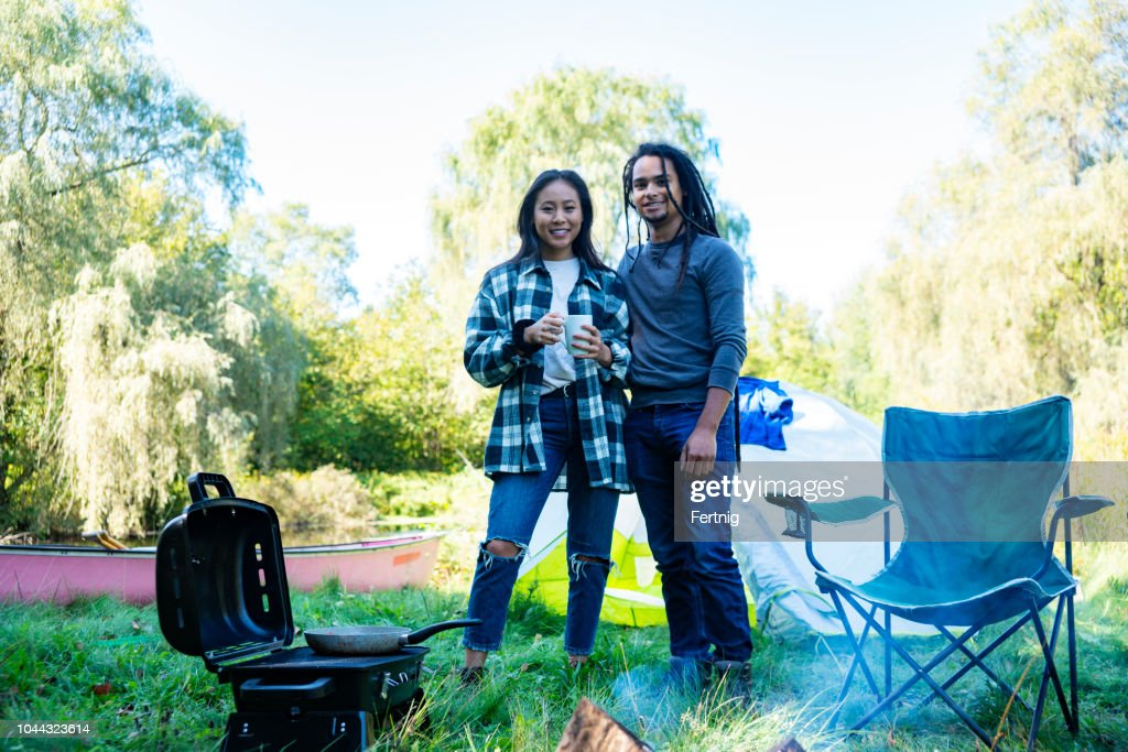 Camping Trip A Cute Couple Posing By A Campfire High-Res ...