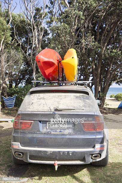 Camping View of my dirty dusty car parked at a campground in the Coromandel North Island New Zealand with two sea kayaks on the roof rack