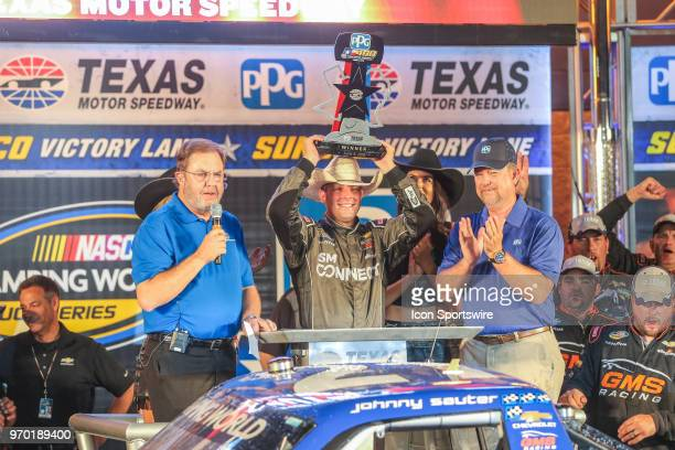 Camping World Truck Series driver Johnny Sauter raises the trophy in Victory Lane after winning the PPG 400 on June 8 2018 at Texas Motor Speedway in...