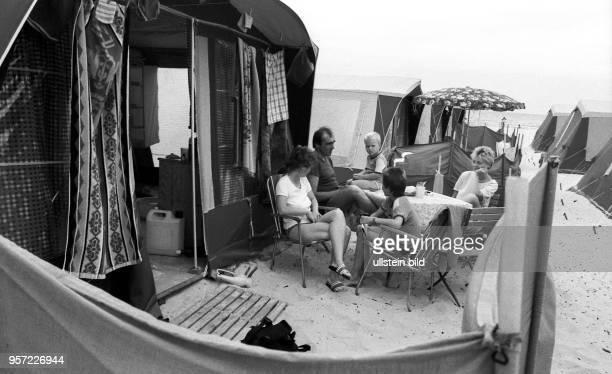Campingfreunde sitzen vor ihrem Zelt auf dem Campingplatz im Ostseebad Prerow auf dem Darß aufgenommen im Juli 1983 Der Zeltplatz in Prerow ist der...