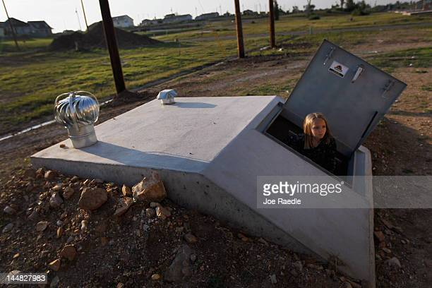 Camryn Dean plays in the newly built tornado shelter behind her mother's rebuilt home in the heart of what was once nothing but debris and destroyed...